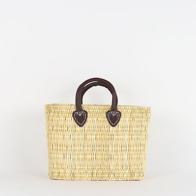 front of our reed basket medium size, natural color and brown handles made from vegetable tanned leather