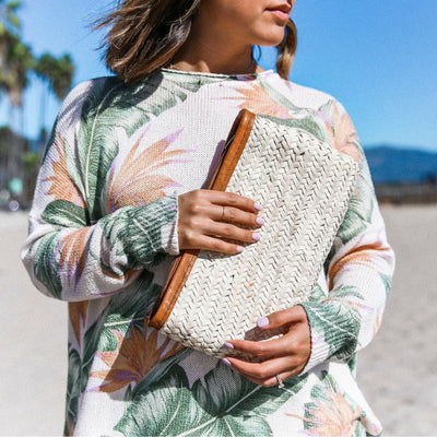 Worn by hands on the beach our Barcelona Straw clutch with leather details