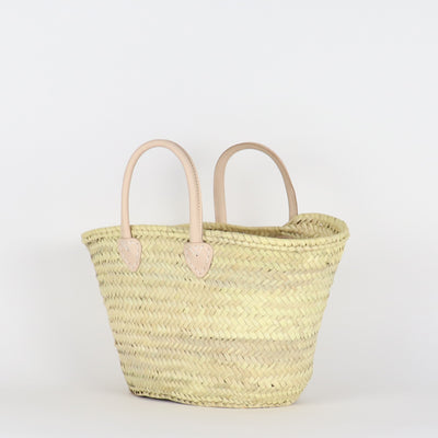 Handwoven palm leaves and vegetable tanned leather round handles market bag in medium capacity from side view