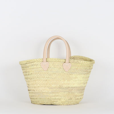 Front of our medium santiago french basket in natural color with round leather handles and handmade straw