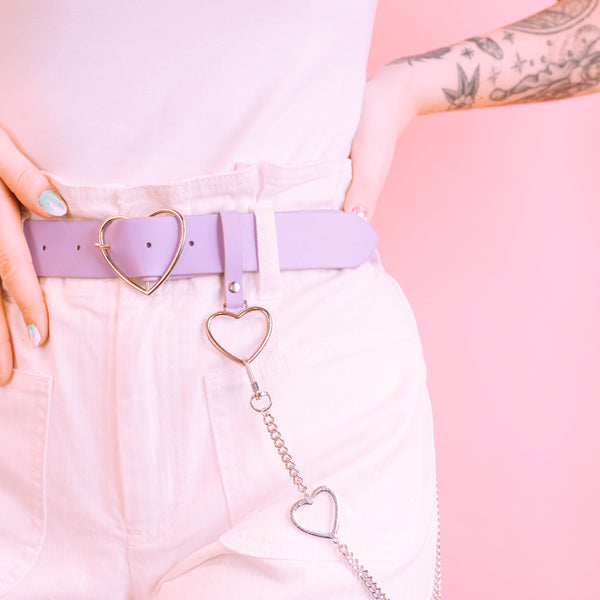 Detail photo of Lavender Sweetheart Belt. Lavender vegan leather belt with silver heart shaped details modeled with a white shirt and white shorts.