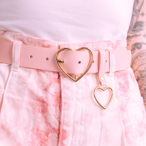 Detail photo of Pink Sweetheart Belt. Soft pink vegan leather belt with gold heart shaped details modeled with a white shirt and pink tie-dye shorts.