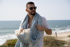 Man with a gwery honeycomb blue beach towel