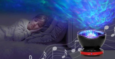 Young blonde boy asleep with a calming sea lamp on the bedside table