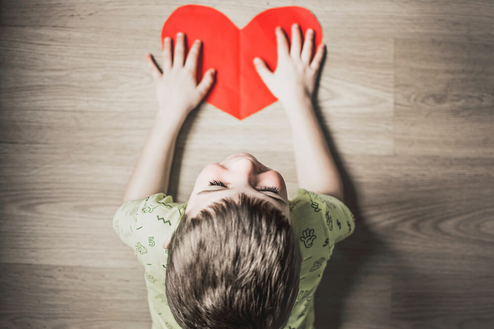 A child with autism holding a heart-shaped paper