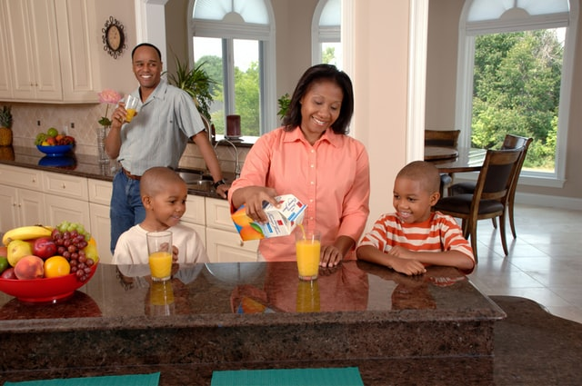 A mother pouring orange juice for two boys