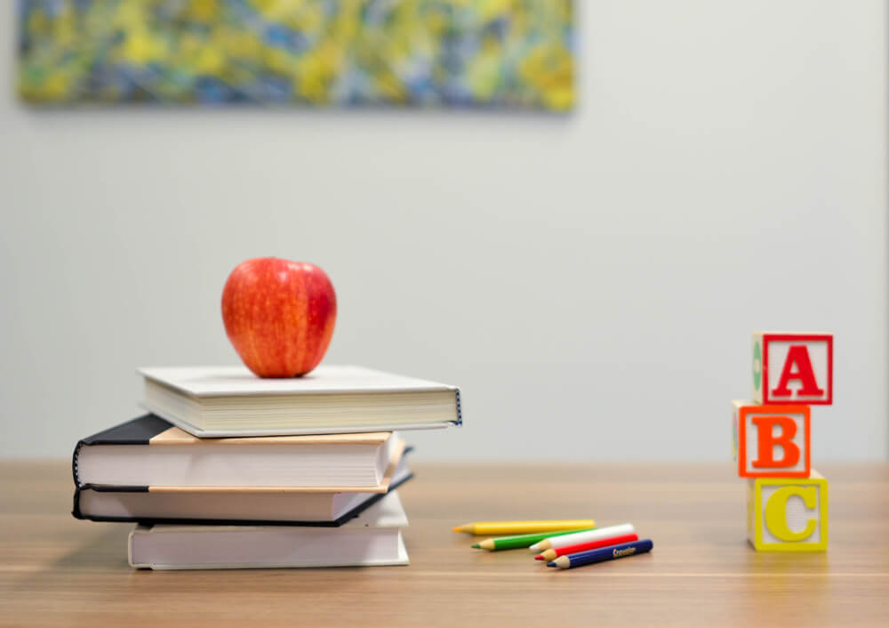 A teacher's desk with an apple, books, colored pencils, and blocks
