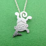 Dangling Cheeky Monkey With A Banana Shaped Pendant Necklace in Silver | DOTOLY