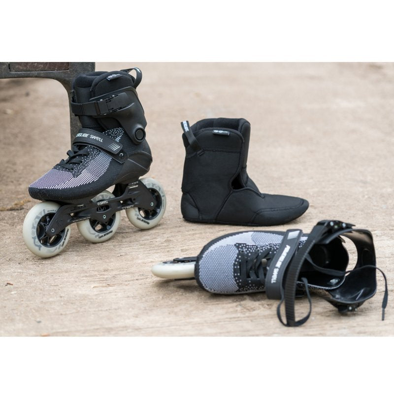 Powerslide Swell Lite Black 1OO Inline Skate outdoors, with one skate on it's side and the soft inner liner next to it.
