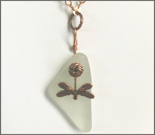 Handmade jewelry by Dee Van Houten. Handmade raw copper, genuine sea glass necklace, A Copper dragonfly charms is designed with the sea glass.