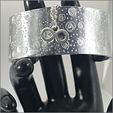 "DevaArt Studio Artisan Handmade Jewelry - ""INFINITY"" is a decorative artisan handmade cuff bracelet designed in a freeform style. The cuff has been hand-etched and hand-hammered for a textural look. The wire-wrap is sterling silver with a sterling silver infinity symbol added"