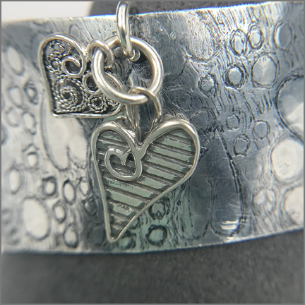 "DevaArt Studio Handmade Jewelry - ""LOVE"" is a handmade cuff bracelet, 1"" wide light-weight aluminum cuff; hand-textured, hand-etched with a free-form heart design. There are two sterling silver heart charms that have been added to the cuff."