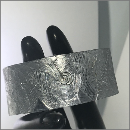 DevaArt Studio Artisan Handmade Jewelry - This decorative artisan handmade cuff bracelet was designed in a freeform style. The cuff has been hand-etched and hand-hammered for a textural look. The wire-wrap is sterling silver with a sterling spiral symbol added.
