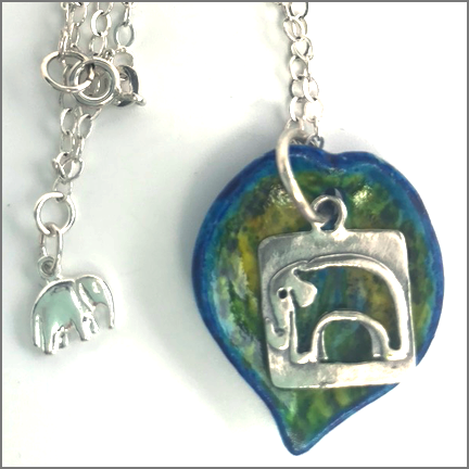 "DevaArt Studio Handmade Fine Art Jewelry - ""Elephant"" - hand-painted ceramic leaf with yellows and blues. Beautiful sterling silver elephant charm hangs from the leaf. Sterling silver oval chain necklace with sterling elephant charm."