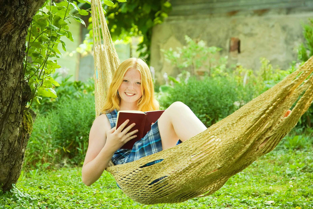 Summer Activity - Girl Reading Book in Hammock
