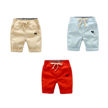 Image of 3 shorts.  Left to right: khaki, light blue and red-orange shorts with embroidered navy blue dog on left front pocket.