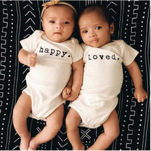two infants: left infant wearing happy print onezie and right infant wearing loved print onezie