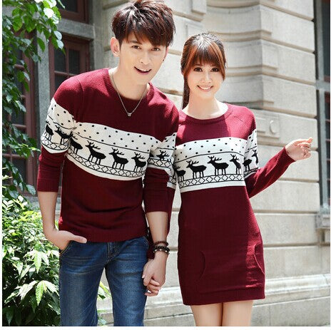 couple wearing matching red christmas sweaters, front view