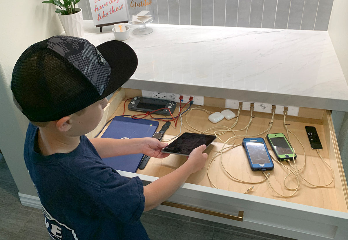 Kid plugging ipad into Docking Drawer kitchen in drawer outlet