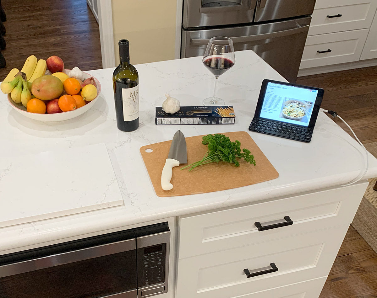 Tablet charging while Tom is cooking