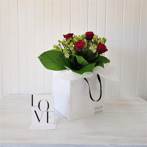 six roses in a gift bag