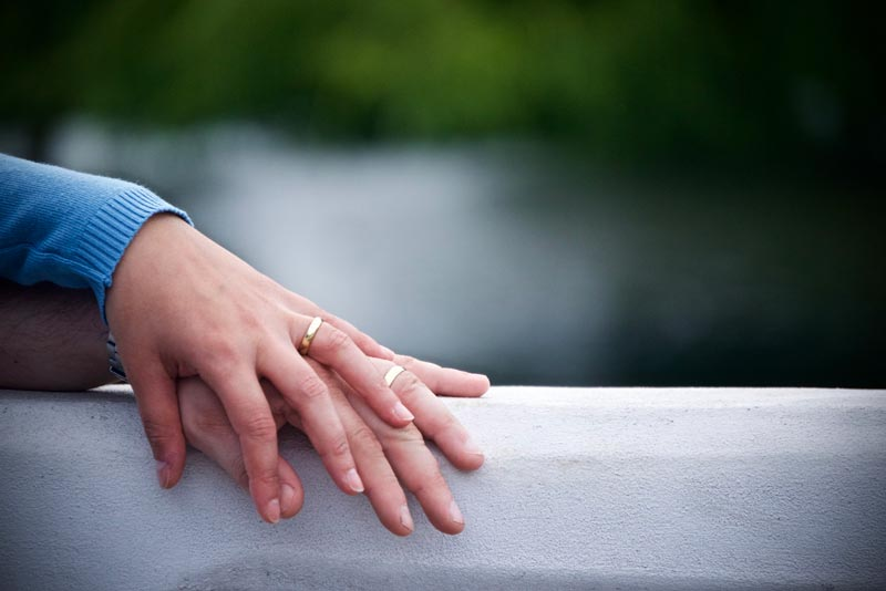 Two hands with wedding bands.