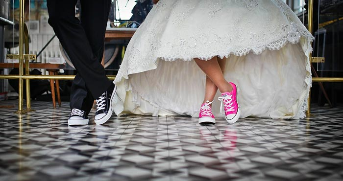 A couple in wedding attire wear lace sneakers.