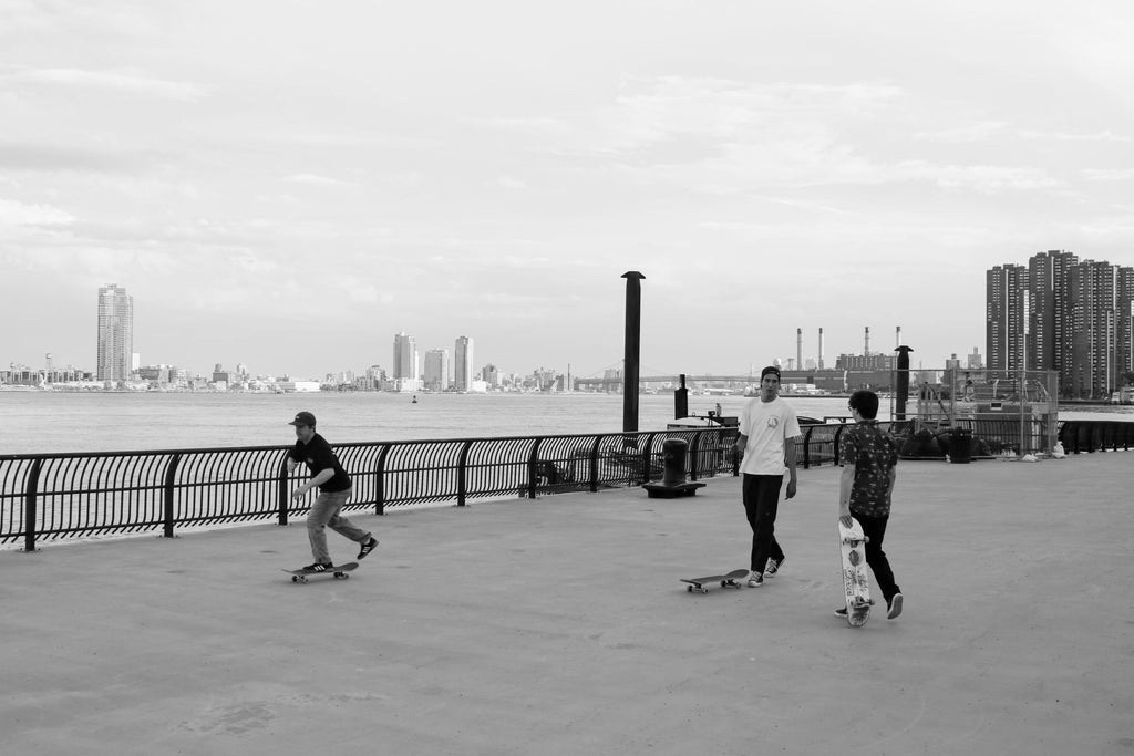 Friends pushing on skateboards in New York