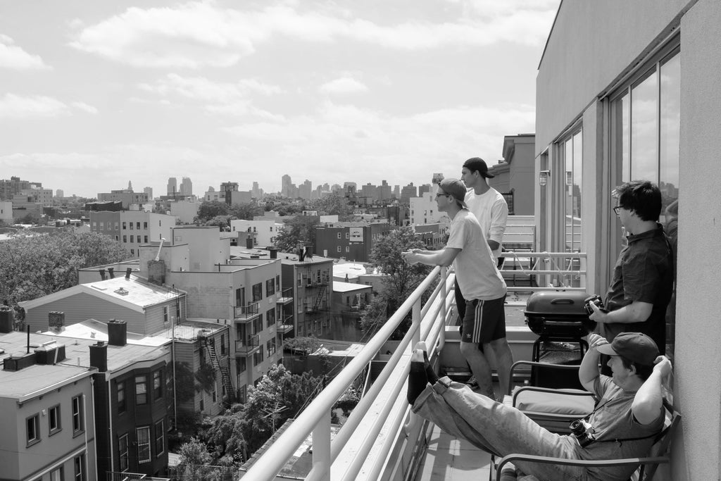 Friends on a balcony overlooking New York