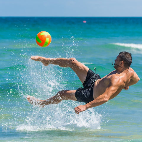 Energetic man playing with a ball on the beach