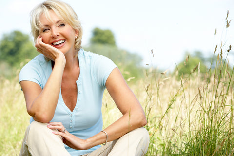 Smiling mature lady sitting in a field looking very content