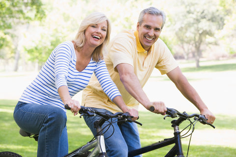 Happy looking couple cycling in a park