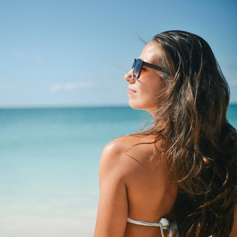 Woman soaking up some Vitamin D from the sun on a beach
