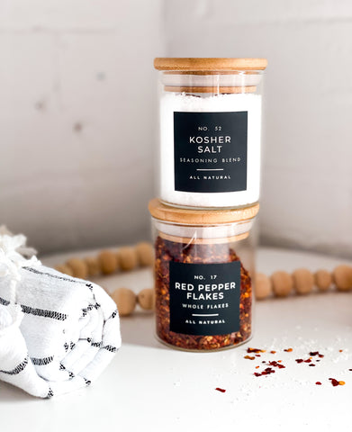 stacked jars of kosher salt and red pepper chili flakes with onyx labels next to a striped tea towel and line of wooden beads