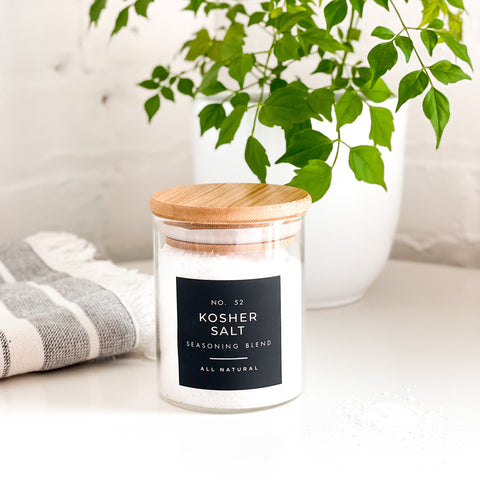 kosher salt black label next to a striped tea towel and a green plant