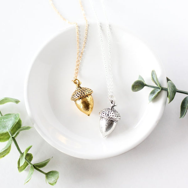 Silver and gold-plated acorn necklaces laid inside a while ceramic dish with green foliage delicately placed next to the dish