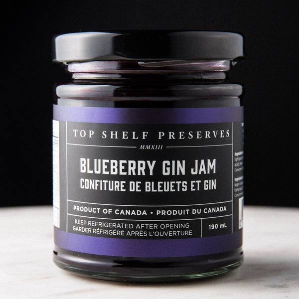 A closeup of a 190ml glass jar with a black top and a black label filled with Blueberry Gin Jam sitting on a marble table in front of a black background