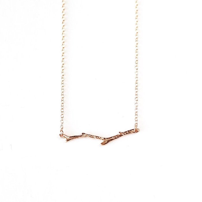 A gold-plated branch necklace laid against a white background