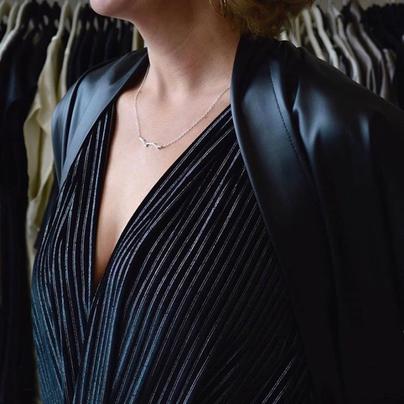 A woman in all black wearing a silver-plated branch necklace