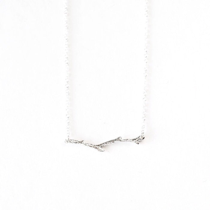 A silver-plated branch necklace laid against a white background