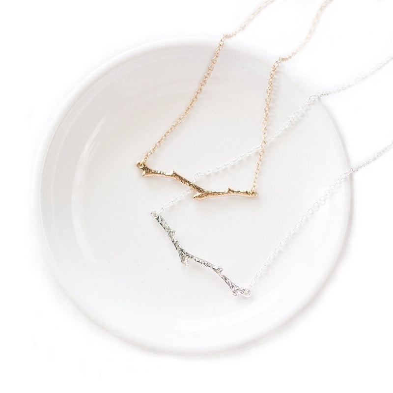 Silver and gold-plated branch necklaces laid in a white ceramic dish