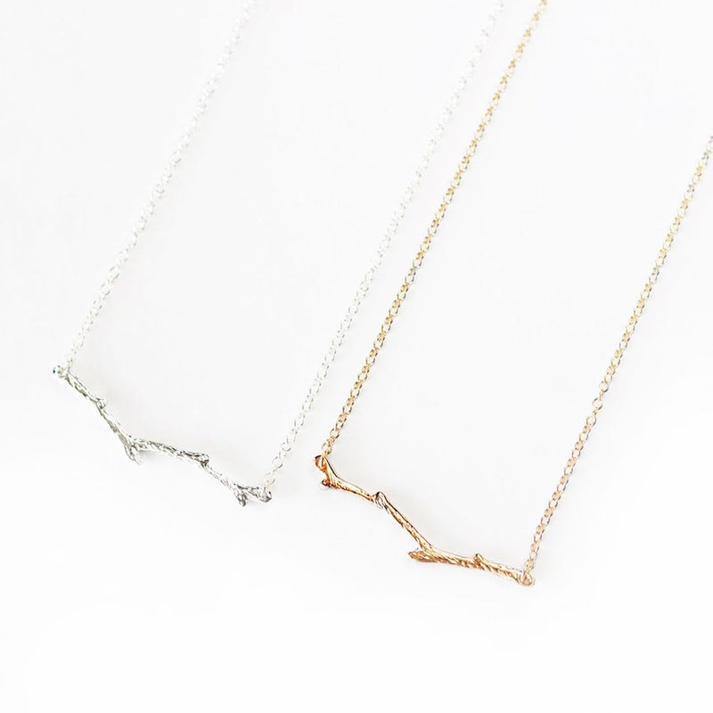 Silver and gold-plated branch necklaces laid flat against a white background