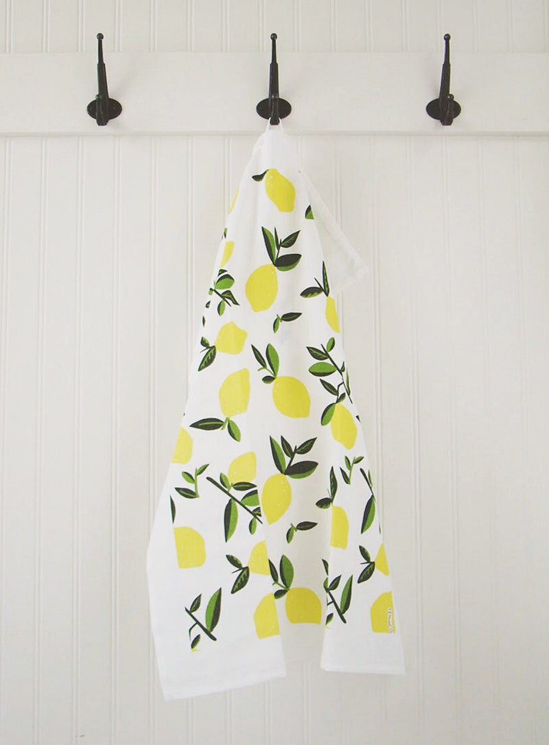 A cotton-linen blend tea towel with citrus lemon print hanging from a black hook against a white wooden wall