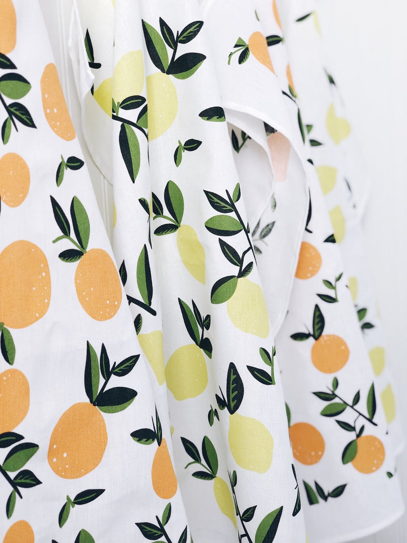 Closeup of Citrus Lemon & Citrus Orange Tea Towels hanging on rack