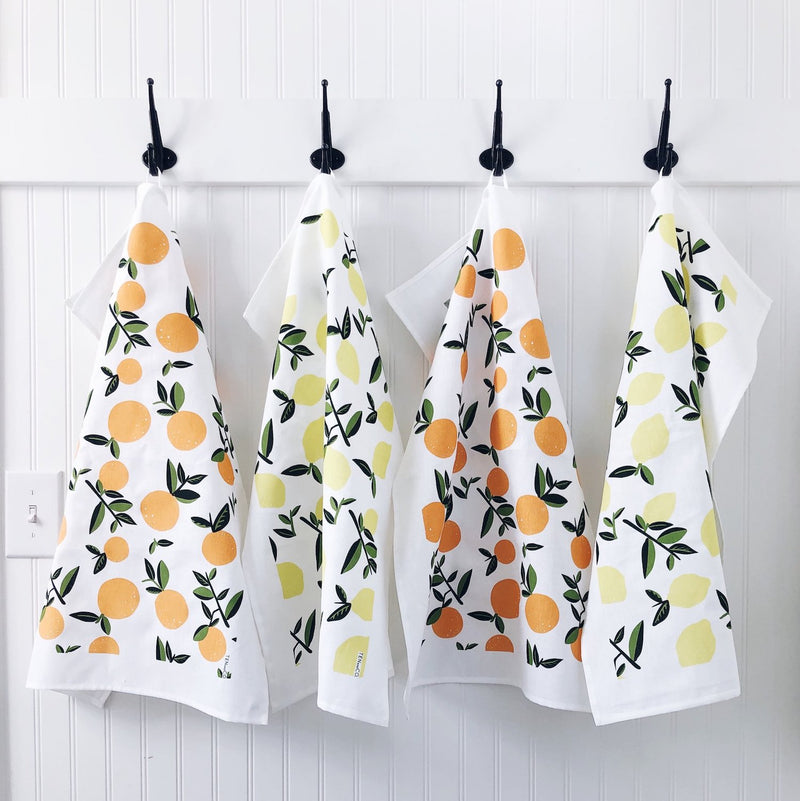 Citrus lemon & citrus orange tea towels hanging on black hooks against a white wooden wall