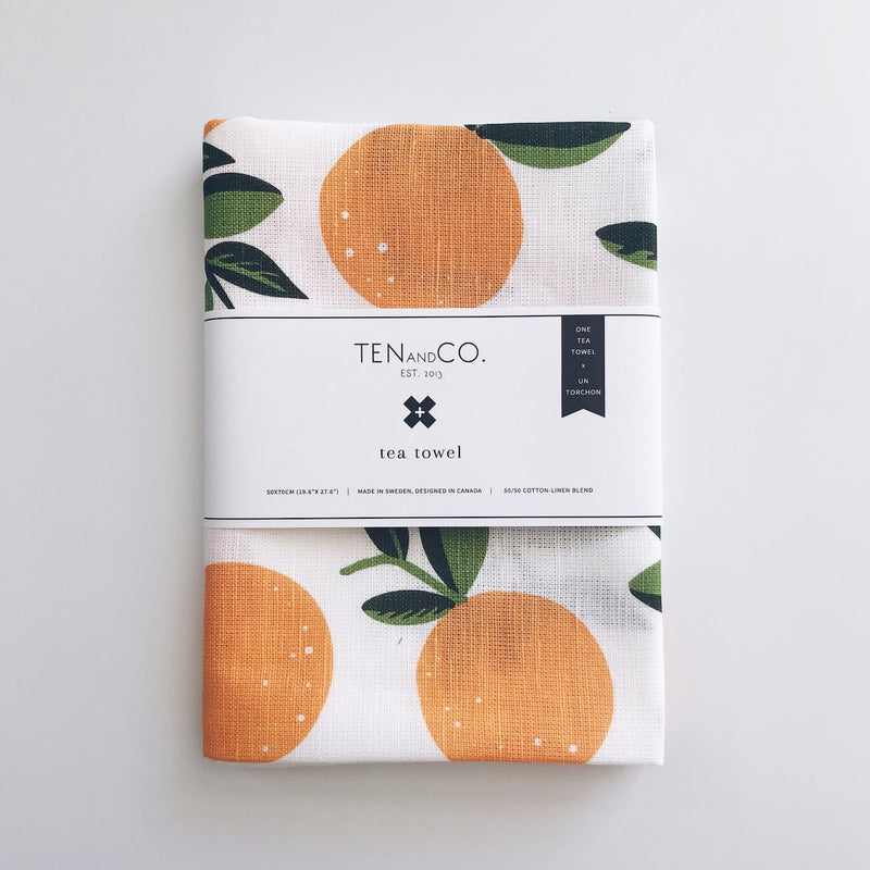 A folded cotton-linen blend tea towel with citrus orange print with a white paper label securing it