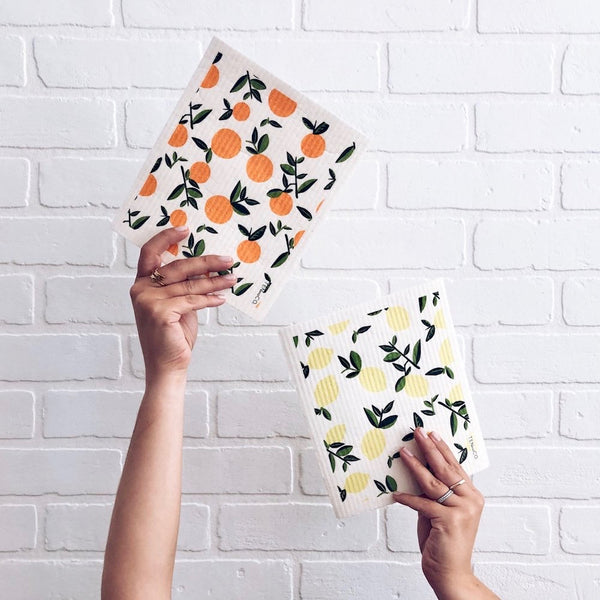 A woman holding two Swedish sponge cloths with citrus lemonade citrus orange prints in front of a white brick wall