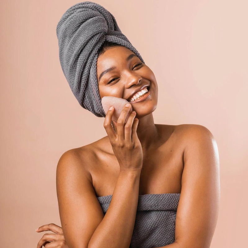A black woman wearing a grey towel and grey head towel smiling as she rubs a Pink Clay Facial Sponge against her cheek