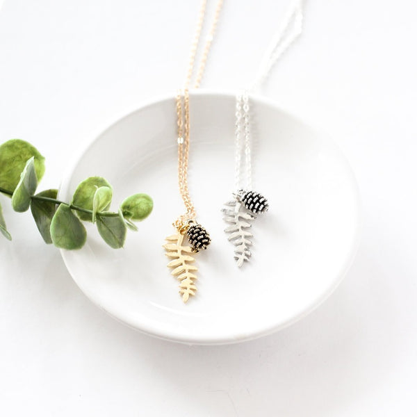 Silver and gold-plated fern leaf & pinecone necklaces laid in a white ceramic dish with green foliage placed beside the dish