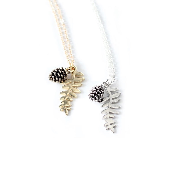 Silver and gold-plated fern leaf & pinecone necklaces laying on a white background